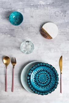 Плоская кладка керамической тарелки и столовых приборов на серый. пустая тарелка. , еда.