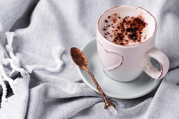 ベッドのある静物シーンで居心地の良い冬の朝の朝食。ウールチェック柄のホットコーヒーまたはココアの蒸しカップ。クリスマス。