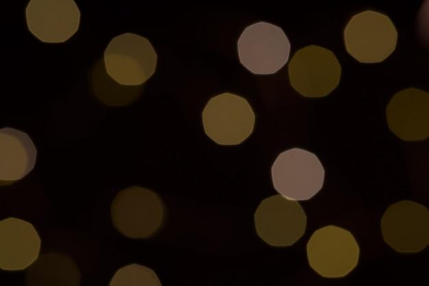 Желтый блеск текстуры боке на черном