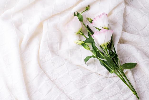 コピースペース、フラットレイアウトの花トルコギキョウと居心地の良いベッドルームブランケット
