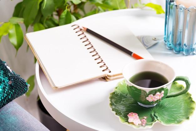 Чашка травяного чая на столе с блокнотом и свечой. интерьер спальни