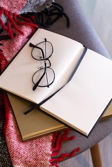 赤い格子縞の眼鏡のノート。コンセプトの快適さ。