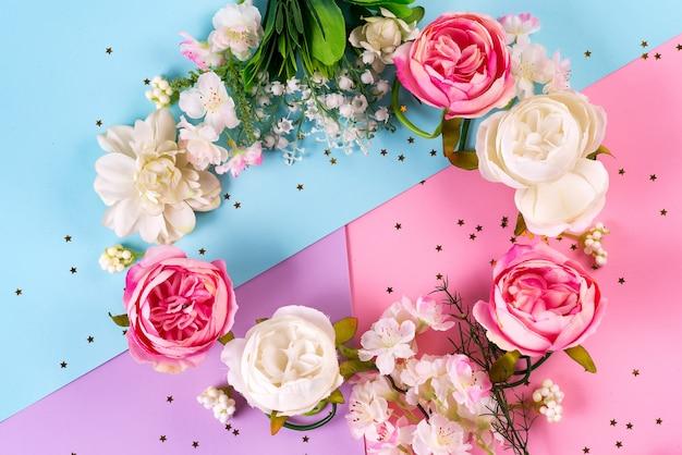 Искусственные цветы на фоне трех цветной бумаги. цветочный венок с золотыми звездами