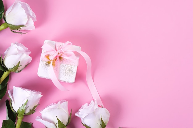 ピンクの背景にピンクのリボンとピンクのバラと白のギフトボックス