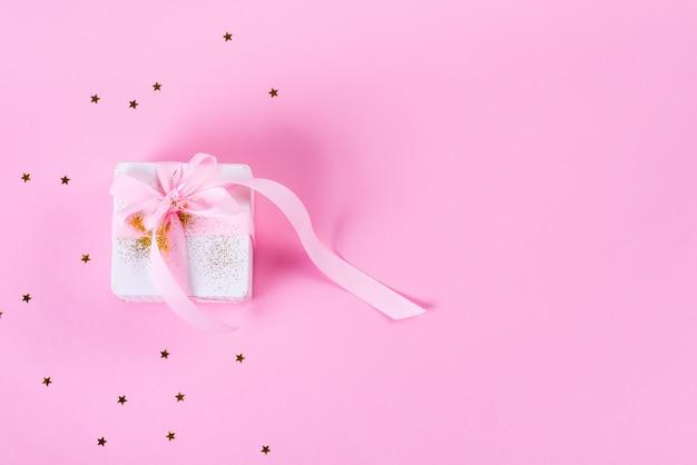 紙吹雪星とパステルピンクの背景にピンクのリボンのギフトまたはプレゼントボックス。フラットレイアウトスタイル。