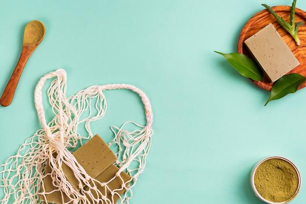 手作りのオリーブ石鹸、緑の葉、青に緑のパウダーが入った再利用可能なショッピングバッグ。廃棄物ゼロのコンセプト。プラスチックなし。