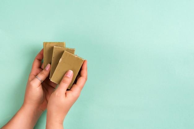 Руки женщины держа естественный органический твердый зеленый бар мыла сделанный с оливковым маслом на сини. ноль отходов дома концепции.
