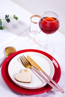 Посуда и украшения для сервировки праздничного стола. тарелки, бокал для красного вина и столовые приборы с зелеными листьями