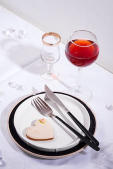 Посуда и украшения для сервировки праздничного стола. тарелки, бокал для красного вина и столовые приборы с печеньем сердца