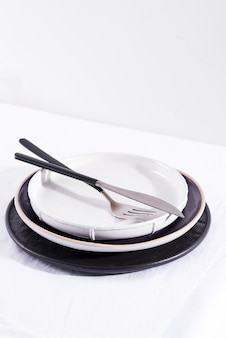 Керамические тарелки и столовые приборы ручной работы на белом текстильном столе, копия пространства