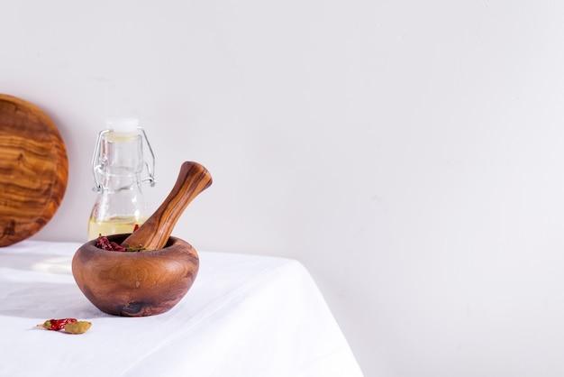 Оливковая деревянная ступка и пестик с перцем чили и кардамоном, изолированные на текстильном столе, копией пространства