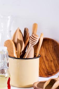 白いテキスタイルテーブルの上の木製プレートと鉄カップで台所用品の木製セット。調理器具。廃棄物ゼロ