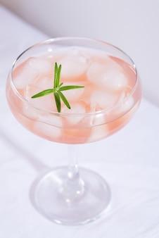 Розовый коктейль с розмарином и льдом на белой скатерти на столе