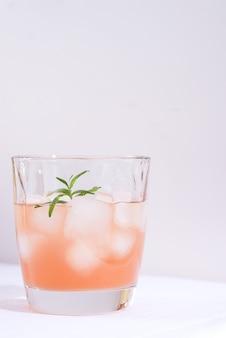 ローズマリーとテーブルの上の白いテーブルクロスの上のガラスの氷とピンクのカクテル