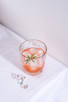 Розовый коктейль с розмарином и льдом в стакане на белой скатерти на столе