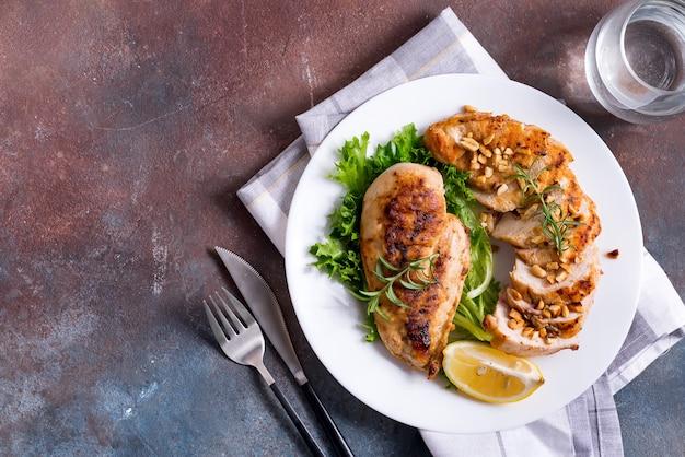 Кусочки куриной грудки гриль и ломтик цельного лимона с салатом. палео диета.