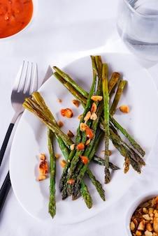 白いプレートに砕いたクルミとソースを添えてオリーブオイルで焼いたアスパラガス。ベジタリアンフード。