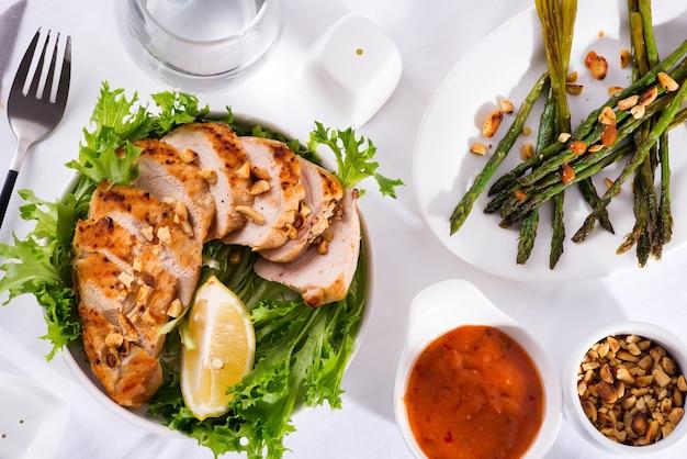 鶏胸肉のグリル、アスパラガスのグリル、レモンスライス。古ダイエット。健康的な栄養。美味しくて健康的な食事のコンセプト。