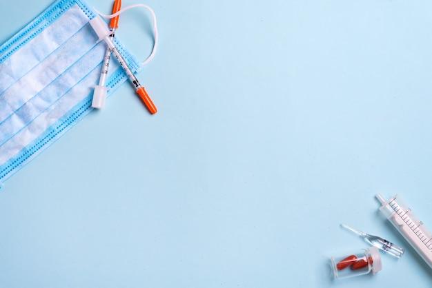 青い医療マスクと使い捨て注射器。医療用品。コピースペース