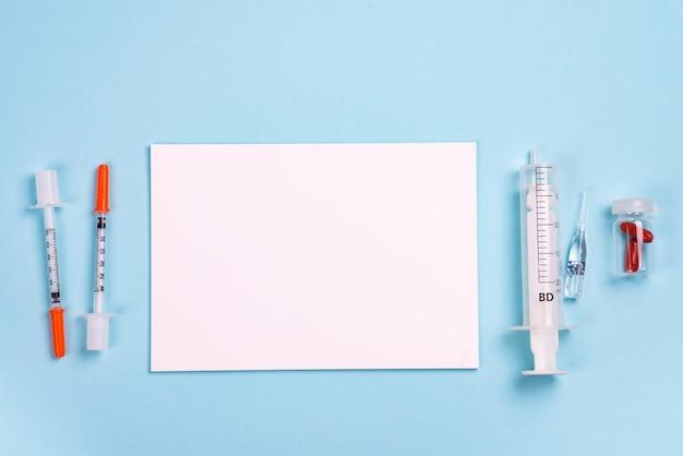 注射器、錠剤、コピースペース付きの紙