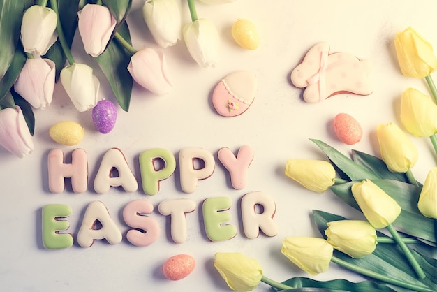 チューリップの花、イースターエッグ、ウサギクッキーとイースターのグリーティングカード。トーンの白い大理石のテーブルの上のトップビュー