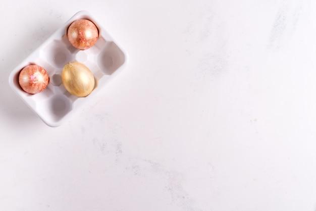 白い石の背景、休日の概念に金塗装イースターエッグとセラミック卵トレイ