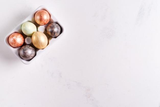 Керамическая подставка для яиц с расписанными золотом и серебром пасхальными яйцами на белом фоне, концепция праздника