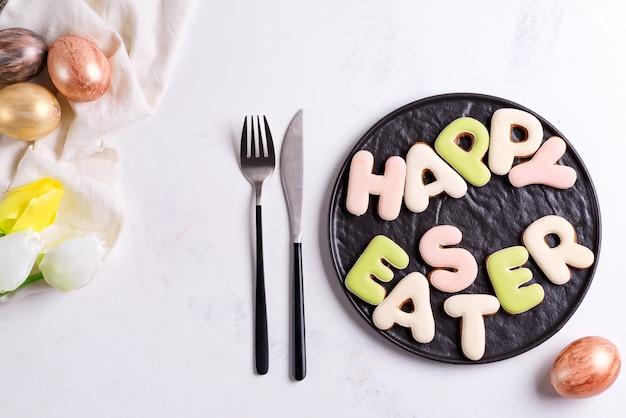 チューリップの花、黄金の卵、プレート上のクッキーとイースターテーブルの設定。白い大理石のテーブルの上のビュー、