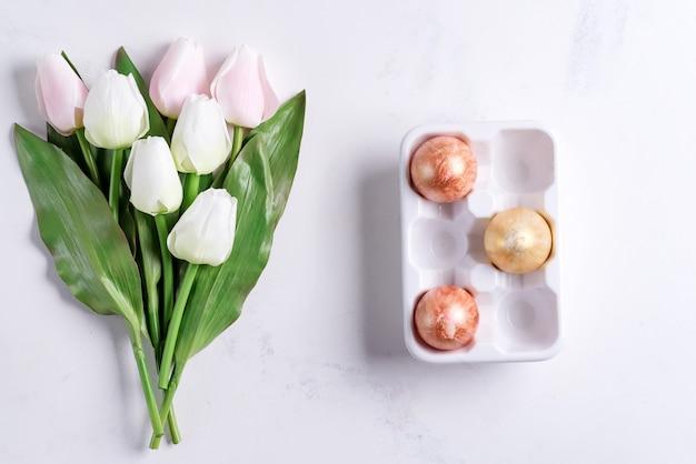石の大理石の表面にパステルチューリップとセラミック卵トレイに黄金のイースターエッグ。