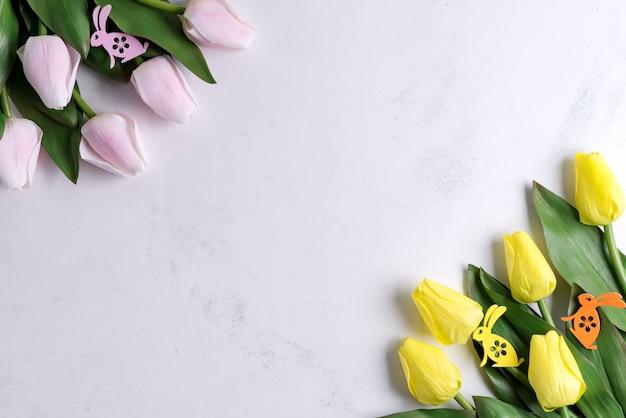 大理石の背景にイースターのウサギと春のチューリップ