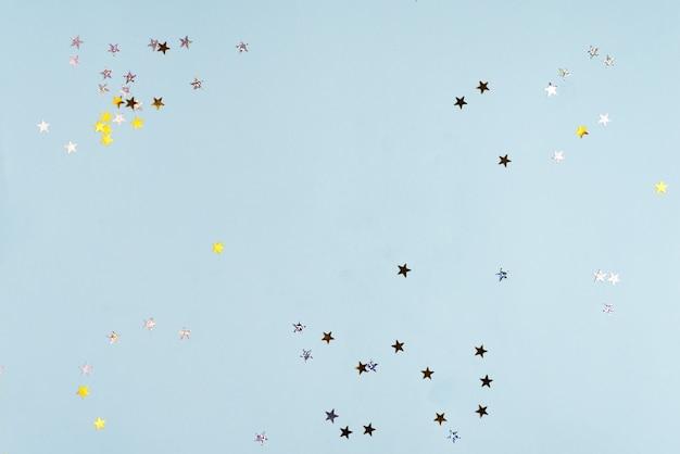 黄金は青いパステル調のトレンディな背景に星を輝きます。プロジェクトのお祝いの背景。