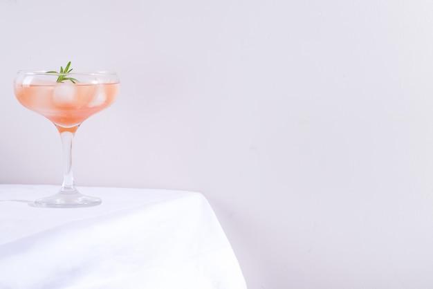 Розовый коктейль с розмарином и льдом в стакане на белой скатерти на фоне стола