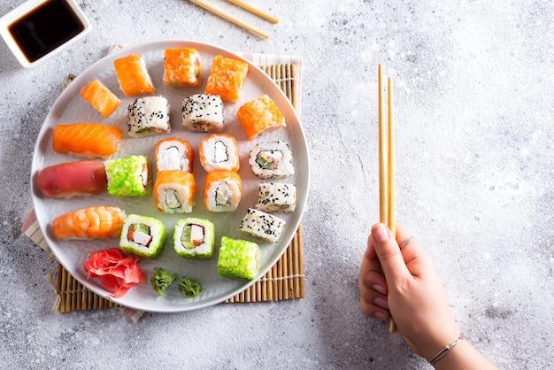Разнообразие свежих роллов и суши с женской рукой, держащей деревянные палочки для еды