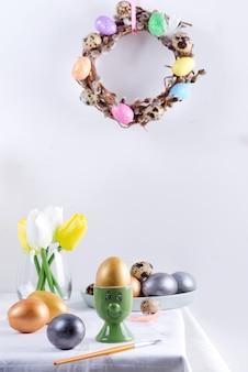Праздничная композиция сервировочного стола с золотым яйцом в зеленой чашке в виде лица, печеного печенья, свежих весенних тюльпанов, цветов и праздничного венка на светло-серой стене. счастливой пасхи концепция.