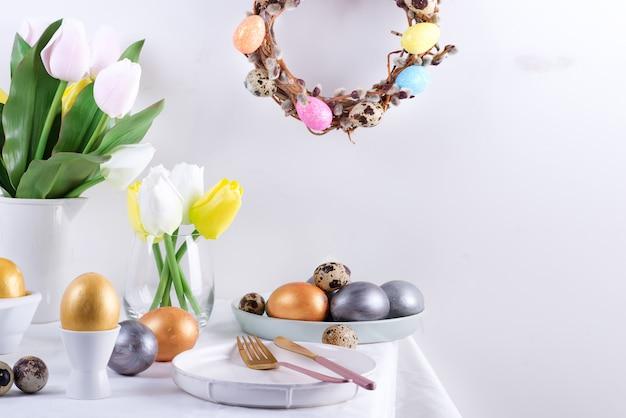 Поздравление с праздничным составом сервированного стола с расписными яйцами ручной работы, печеным печеньем, цветами свежих весенних тюльпанов и праздничным венком на светло-серой стене. счастливой пасхи концепция.