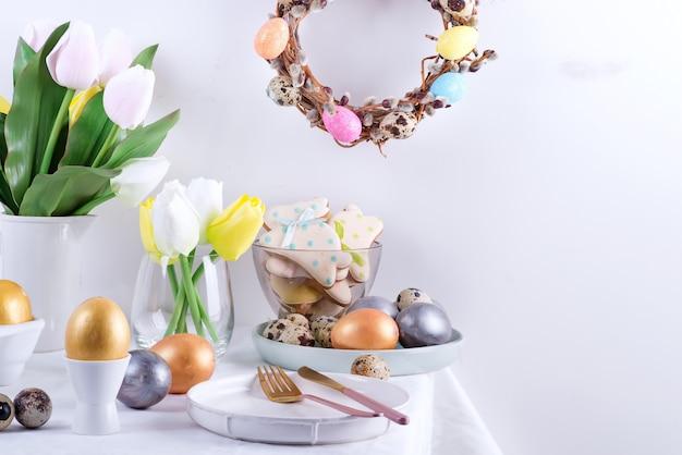 Праздничная пасхальная сервировка с крафтом крашеные яйца, запеченное печенье и свежие цветы на столе покрыты белой тканью.