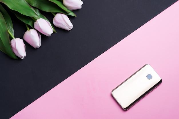 ダブルトーンの対角線の背景に携帯電話と春のピンクのチューリップの花のグリーティングカード。