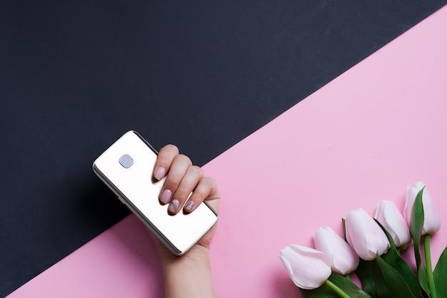 ダブルトーンの斜めの背景に女性の手と春の白いチューリップの花の携帯電話でお祝いカード。