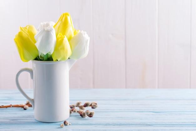 カップに新鮮な春のチューリップの花と明るい青の木製テーブルに新鮮な柳の小枝おめでとうポストカード。