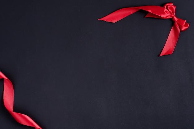 赤いリボンと装飾的な弓からコーナーフレームとお祝いの黒の背景。