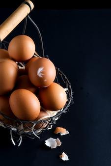 Корзина с близкими поднимающими вверх свежими фермами естественными куриными яйцами на черной поверхности. пасхальная открытка.