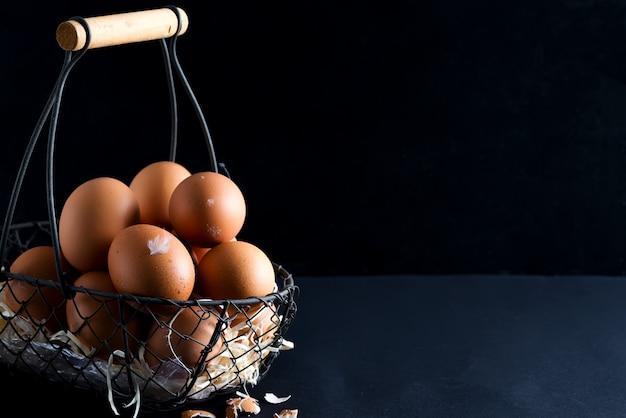 Корзина с близкими поднимающими вверх свежими фермами естественными куриные яйца на черном фоне. пасхальная открытка.