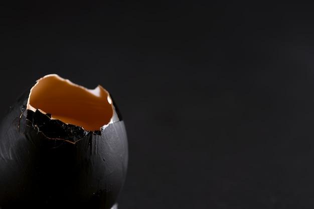 Черное окрашенное сломанное сырое яйцо со свежим желтым желтком на том же цветном фоне.