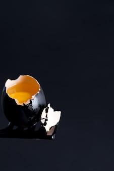 Пасхальная композиция из ручной черной краской сломанного сырого яйца со свежим желтым желтком на фоне того же цвета.