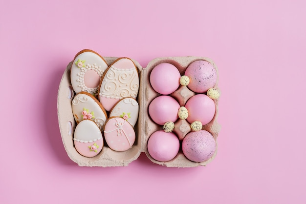 Пасхальная композиция из крашеных яиц в бумажной коробке и печеного печенья на розовом