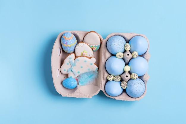 Пасхальная композиция из крафта крашеные яйца в бумажной коробке и запеченные печенье на синем.