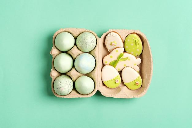 Пасхальная композиция из крафта крашеные яйца в бумажной коробке и запеченные печенье на зеленый.