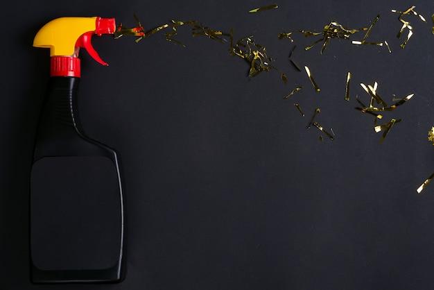 黒に金色の明るい紙吹雪が付いているプラスチックスプレーボトル。