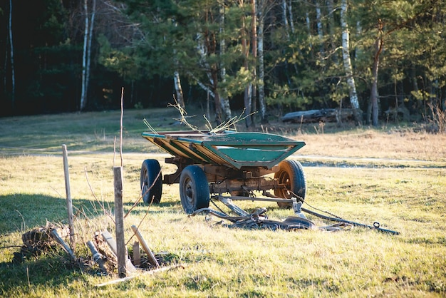 Старая зеленая телега и конная повозка на поле в деревне