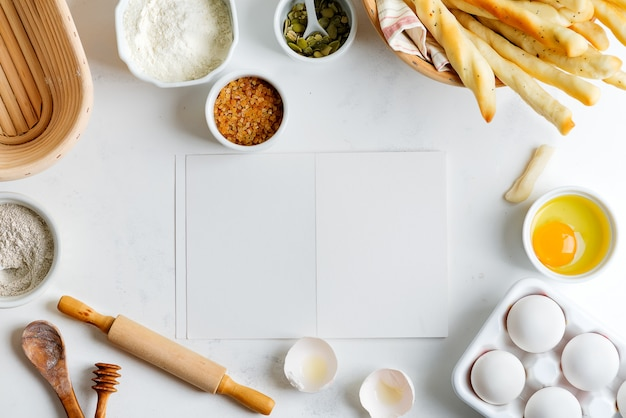 薄灰色の大理石のテーブルでレシピを作るための紙で自家製の伝統的なパンを調理するためのベーキング成分。